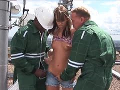 Brunette is fucked outdoors by two electricity guys